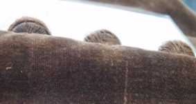 Several of the dress' silk-covered metal buttons had lost most of their fabric covering, and the remaining threads on the most damaged buttons had slid off the surface, and were trapped at their backs.