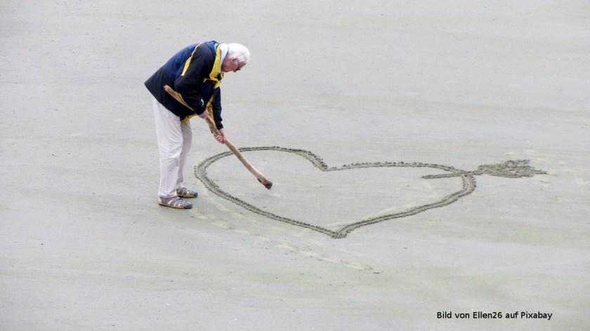 Weisshaariger Mann malt grosses Herz in den Sandstrand