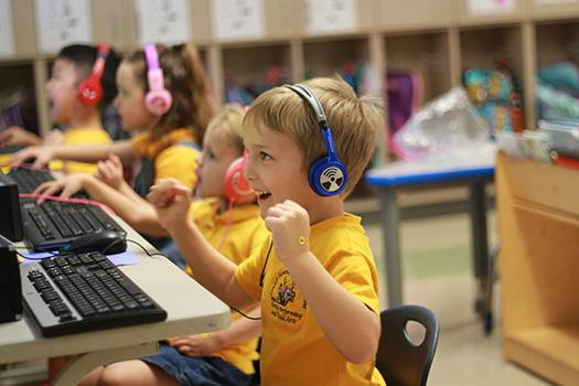 дети в наушниках за компьютерами
