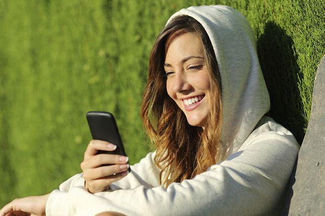девочка играет в компьютерную игру на смартфоне