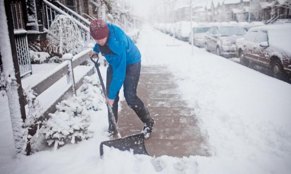 Мужчина с синей куртке чистит снег лопатой