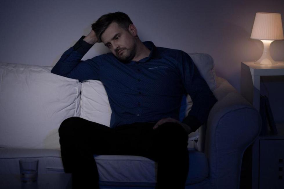мужчина сидит на диване, задумавшись