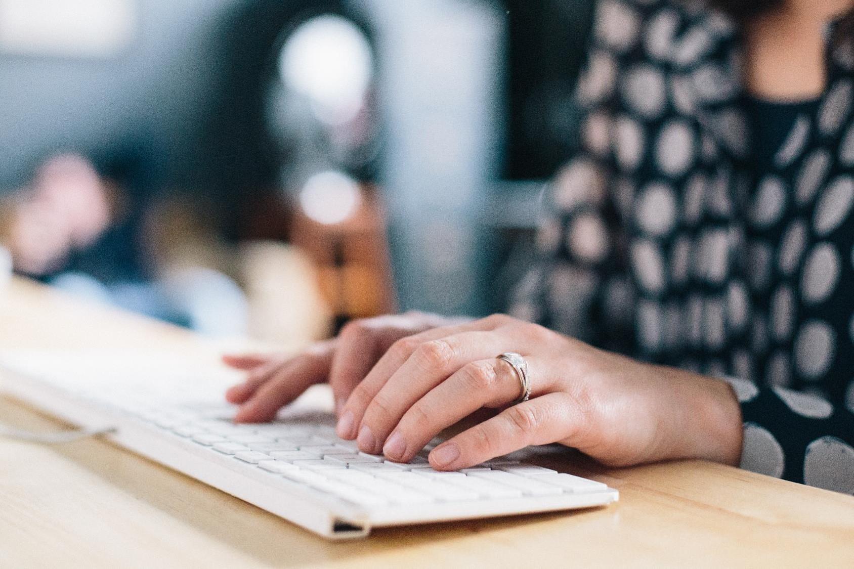 Weibliche Hände an der Computer-Tastatur.