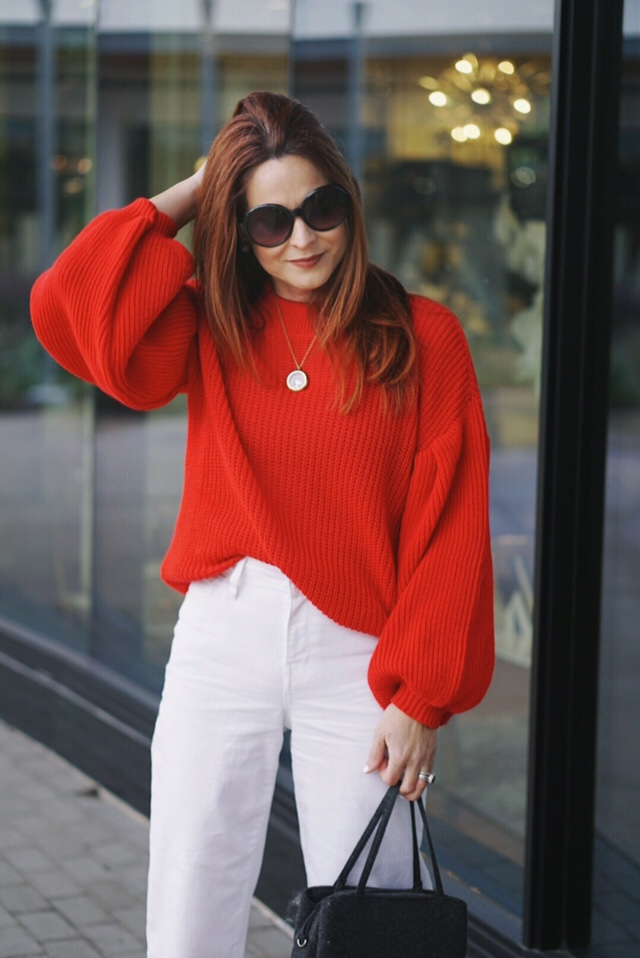 statement sleeves, puffy sleeves, red sweater outfits, wool handbag, black round sunglasses, high waisted white denim
