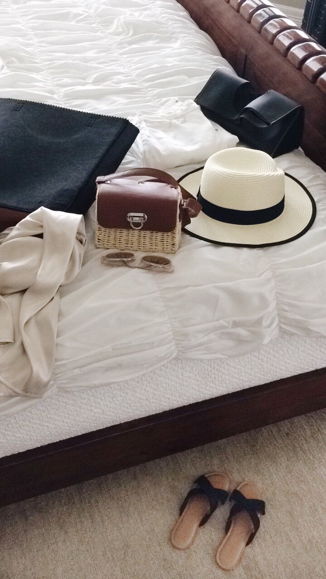 vintage basket bag, straw hat, black tote bag, white bedding, packing essentials, flatlay
