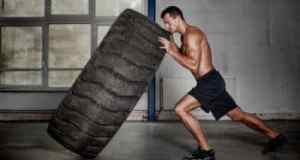 Man pushing a big tire CrossFit workout cut fat and gain muscle