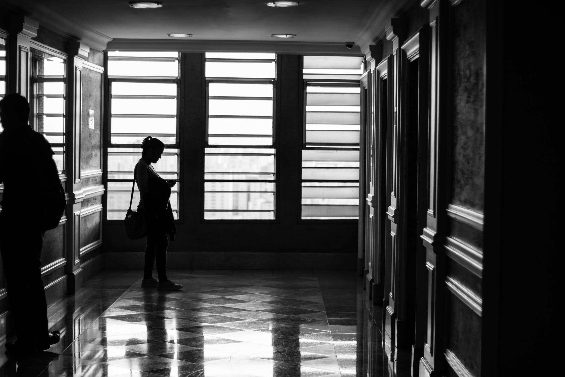 woman waits in elevator lobby to enter in elevator lift