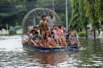 """Thai people travel on a boat through floodwaters as they evacuate the inundated district of Bang Bua Thong of Nonthaburi province, suburban Bangkok on October 20, 2011. Thailand's premier warned October 20 that it was impossible to stop the kingdom's worst floods in decades gushing into Bangkok, ordering the city's sluice gates to be opened to tackle the """"national crisis"""". CHRISTOPHE ARCHAMBAULT/AFP/Getty Images"""