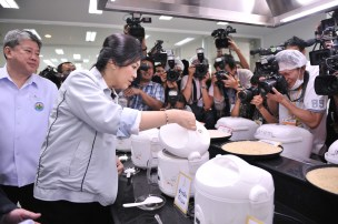 Yingluck checking on cooked rice while photographers take pictures