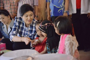 yingluck offering snacks to kids