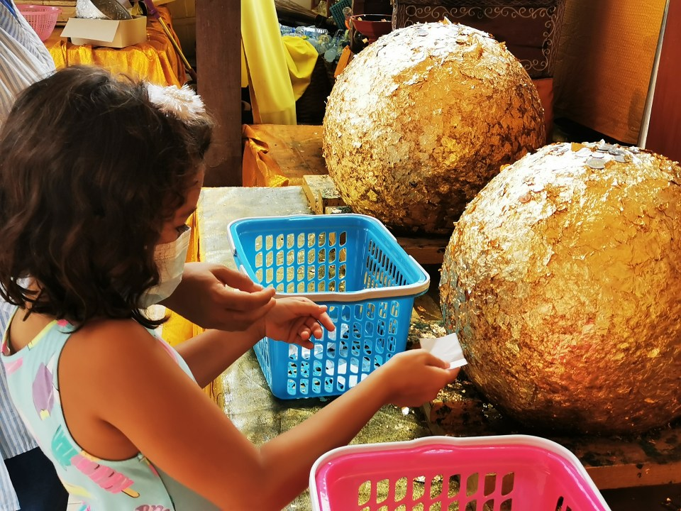 Attaching gold leaf to a ball in the temple.