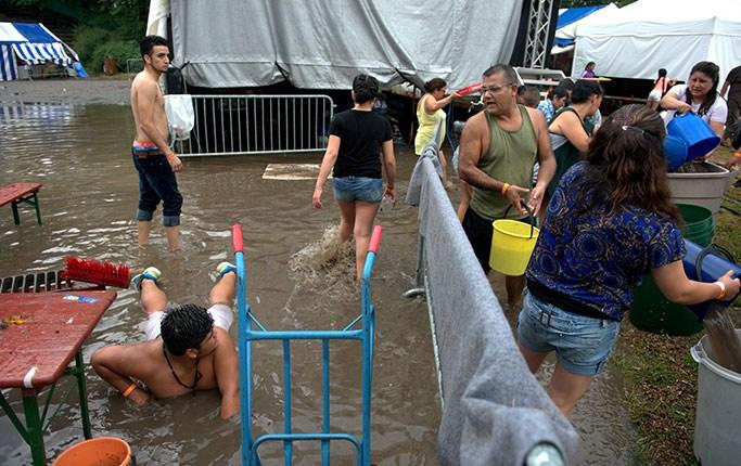 Rålambshovs sommarfestival blir översvämmad. Santiago Hereda öser vatten samtidigt som sonen Sebastian försöker gräva upp brunnen som har täppts igen.