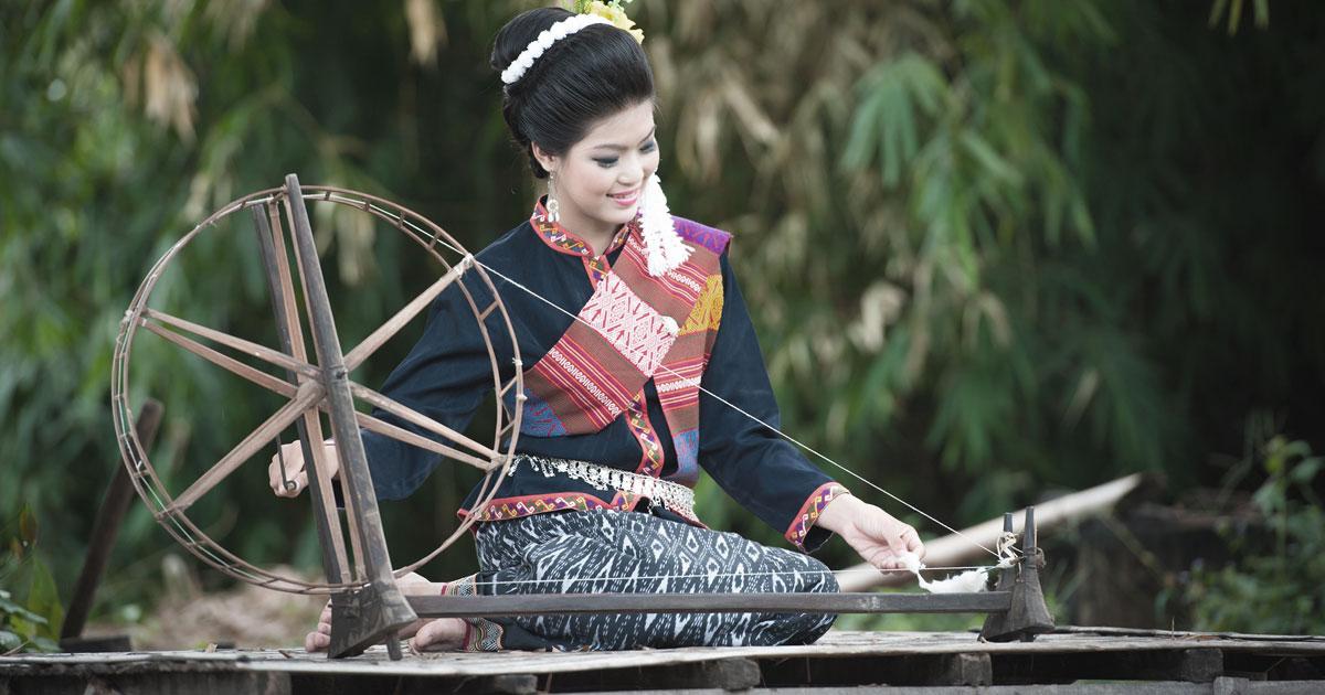 糸車で糸を紡ぐタイ人女性