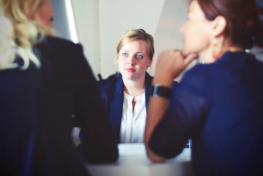 Uma pessoa no centro, observando o que as duas mais para fundo na imagem, estão conversando