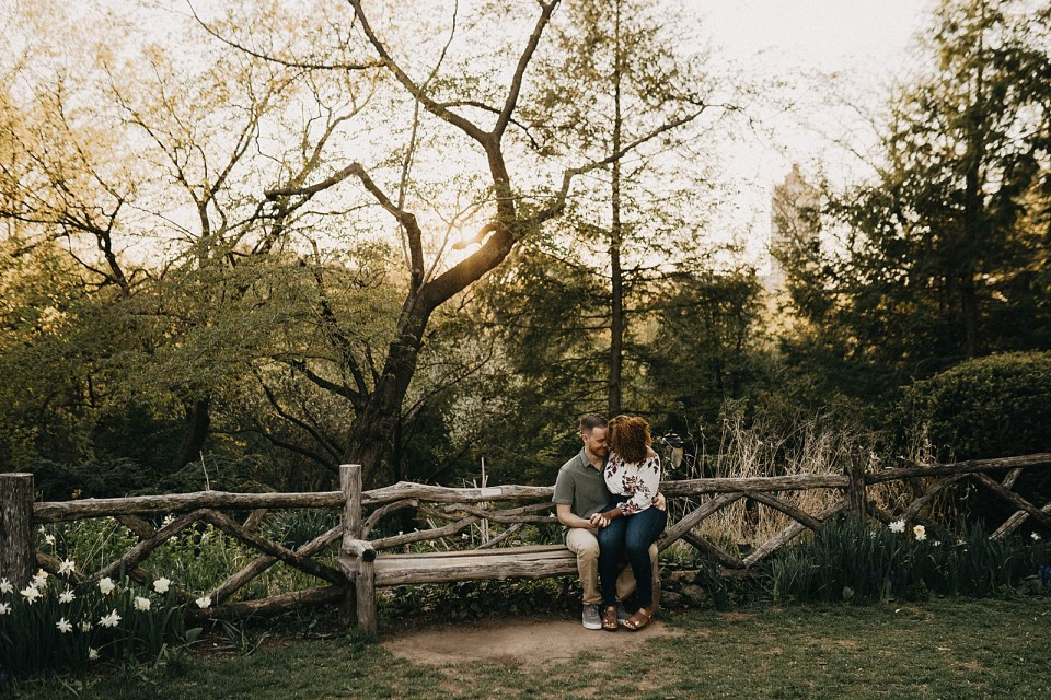 Woman sitting on man's lap on wooden bench in park