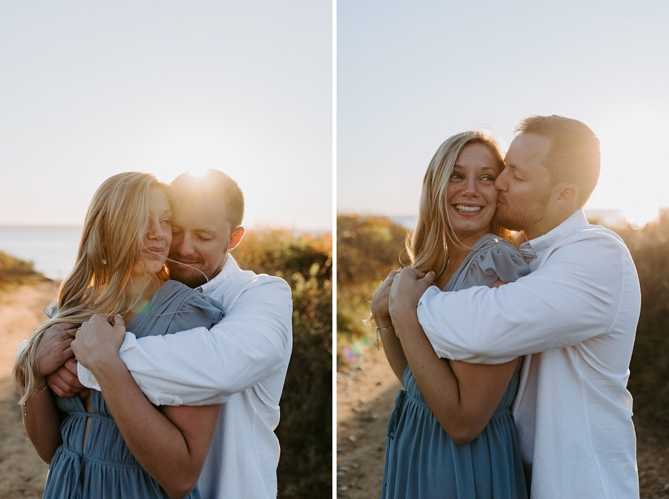 Man wrapping arms around woman with sunset light shining off of them