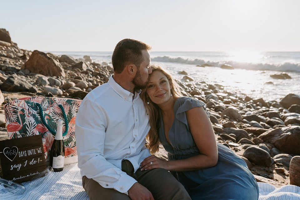 Couple sitting together on smooth rocky shoreline with blanket and Champaign