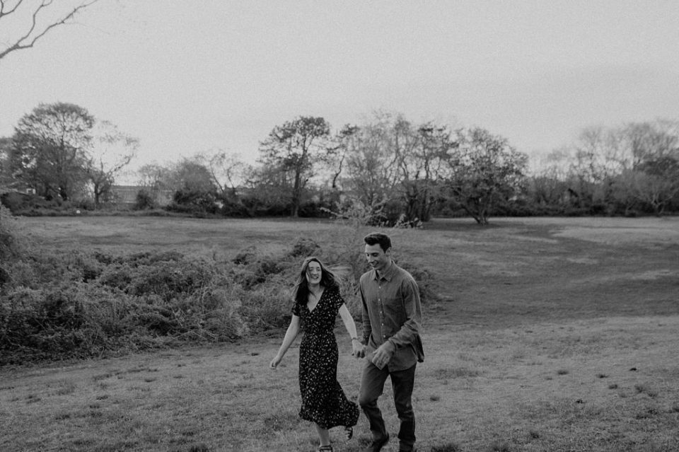 B&W couple holding hands and walking on field together
