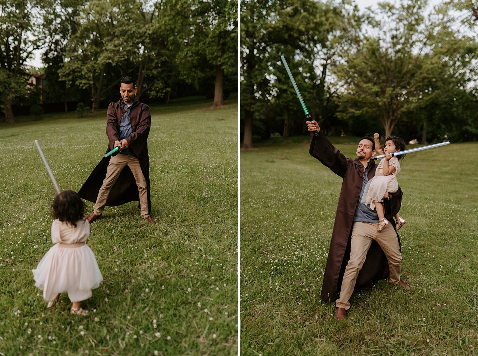 Father and daughter holding lightsabers on grassy field playing