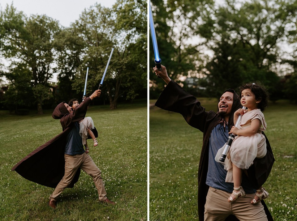 Father holding daughter with both of them holding lightsabers on grassy field