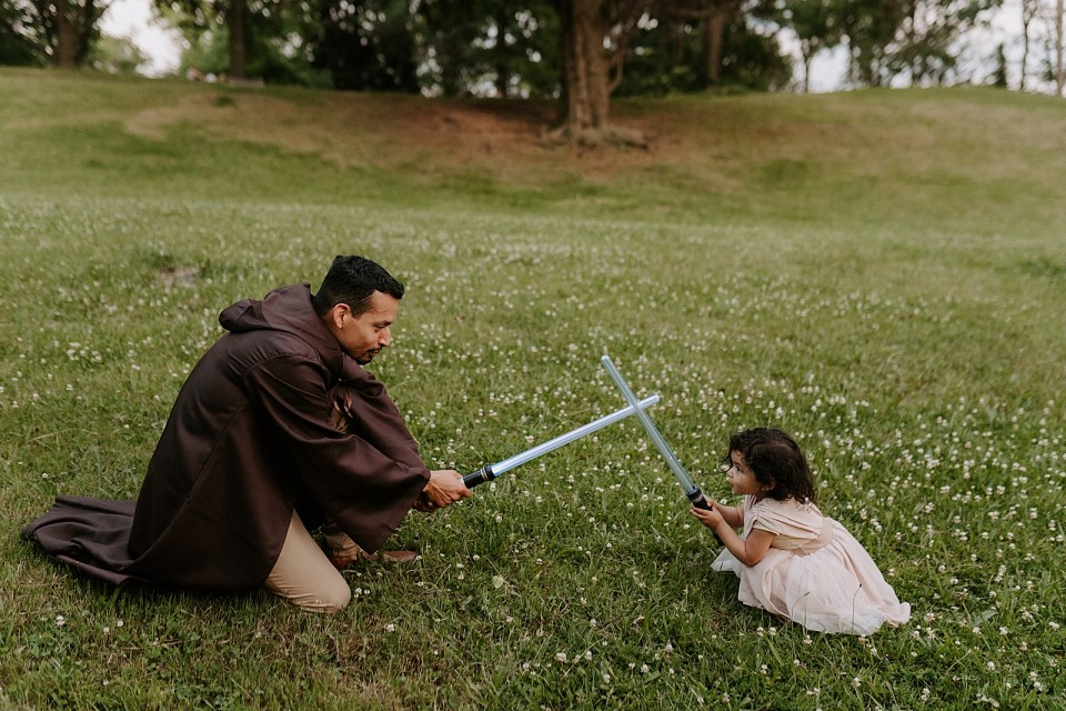 Father and daughter clashing lightsaber on grassy field