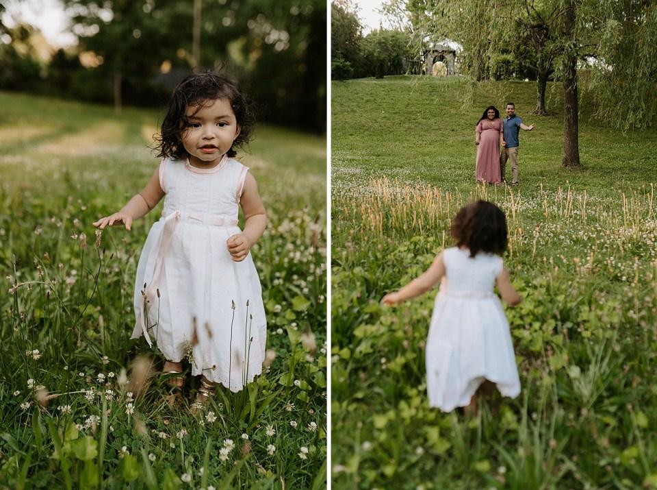 Toddler daughter running on grassy field in dress