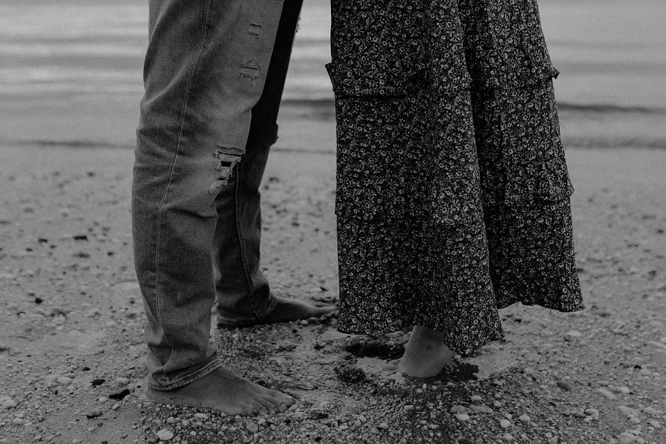 B&W closeup of couple's legs and wet sinking in the wet sand