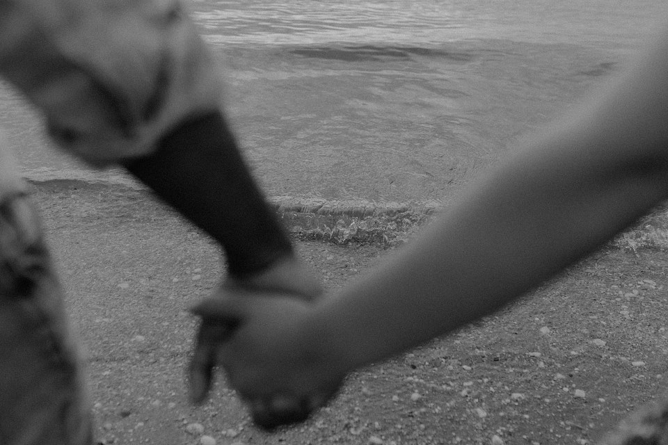 B&W of calm wave coming in on the beach with blurry shot of couple holding hands
