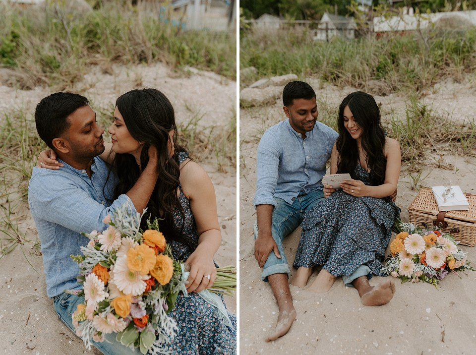 Couple sitting on the sand together and holding each other with bouquet