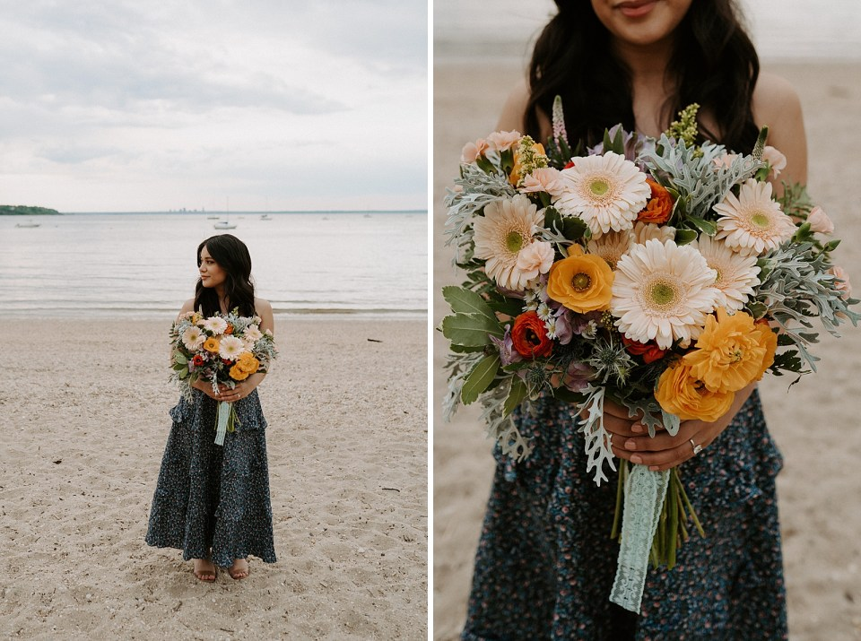 Woman standing on sand in front of the ocean with summer bouquet