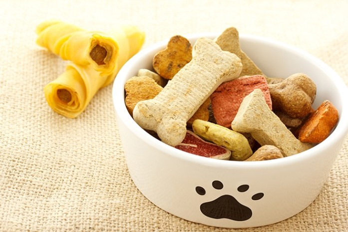 Dog treats in white bowl on burlap cloth