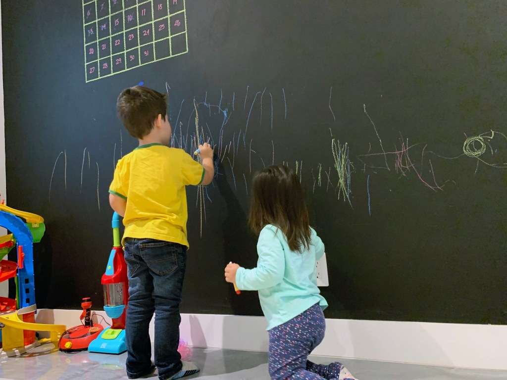 Toddlers Coloring on Chalkboard Wall