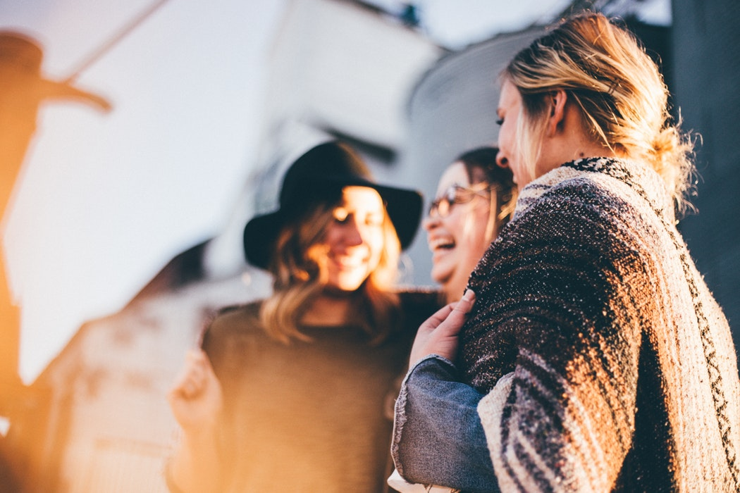 A group of friends laugh together - 23 Things You Should Know Before Visiting The UK