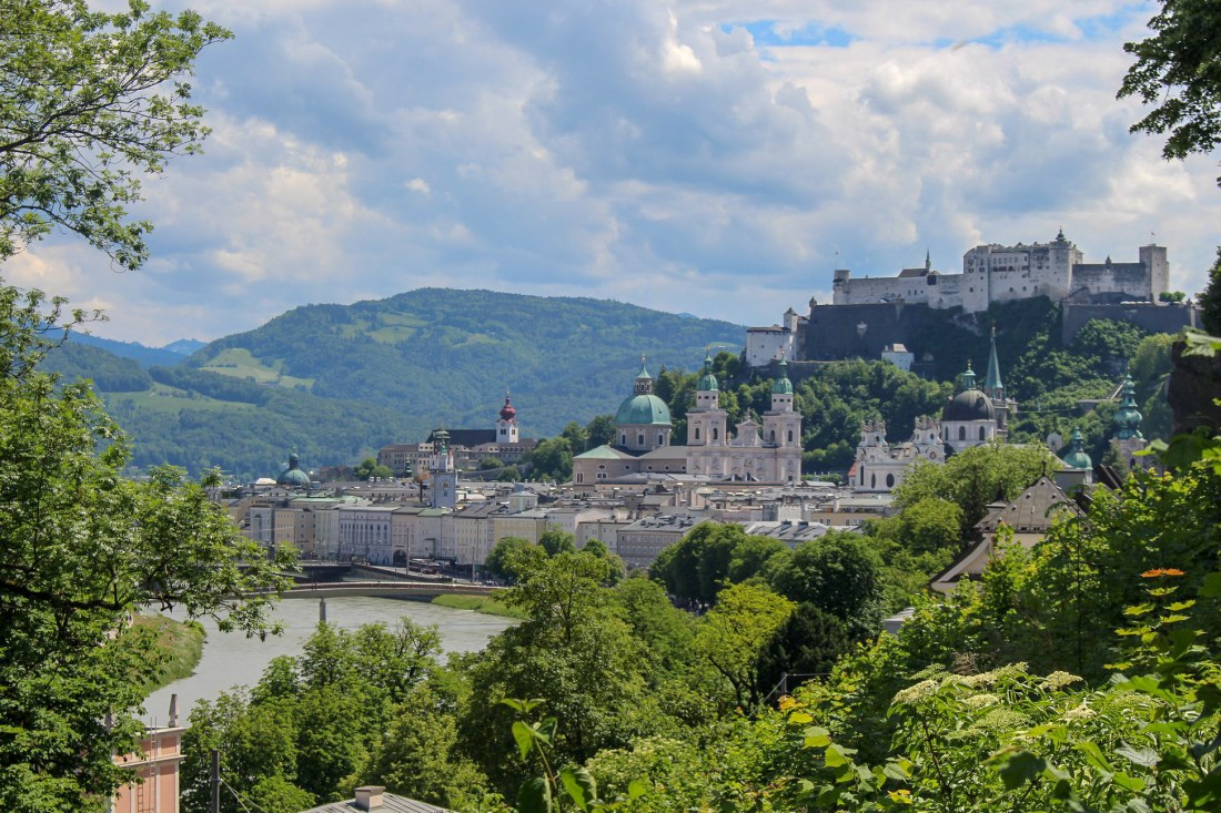 A view of Salzburg in Austria, with the Salzburg Fortress on a hill above a town with domes and spires. Salzburg is perfect for slow travel, and is one of the best city breaks in Europe.