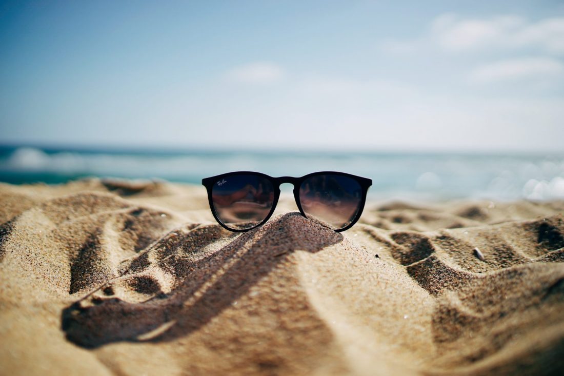 A pair of sunglasses in the sand, by the sea