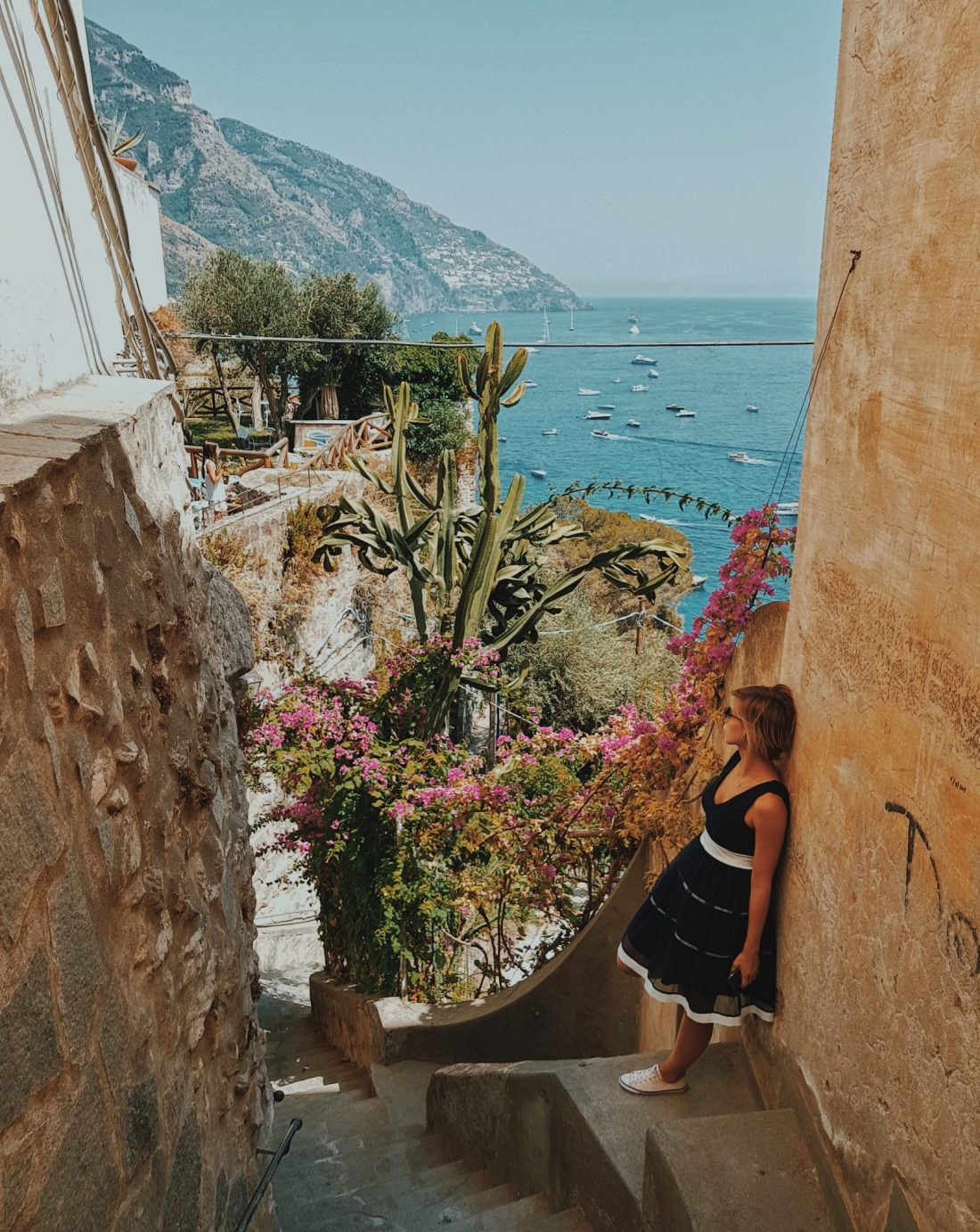 Woman in dress leans against a wall in Positano