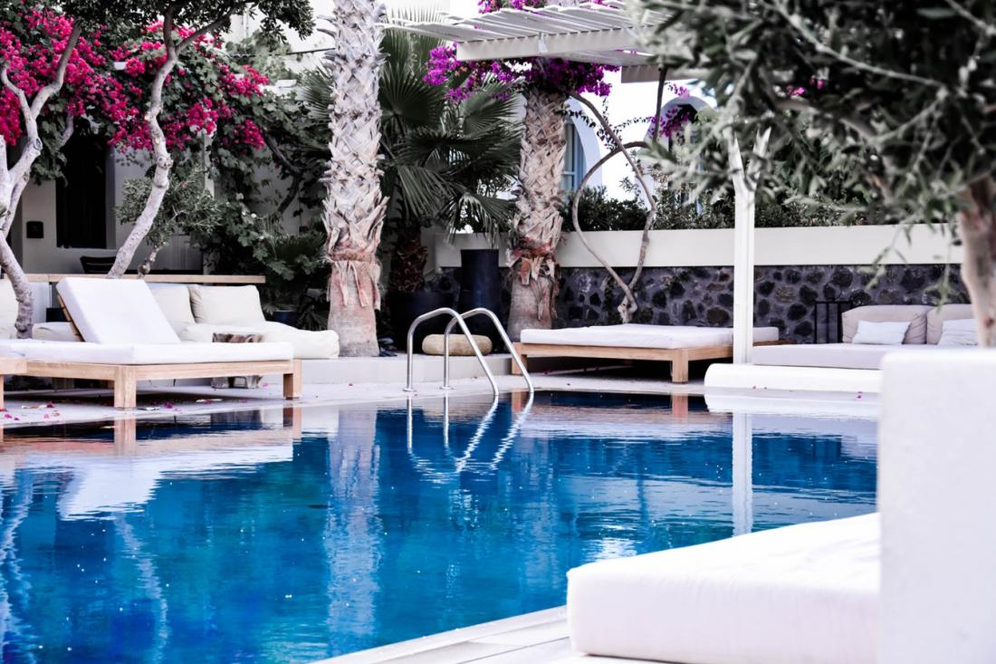A hotel pool surrounded by seats and flowers