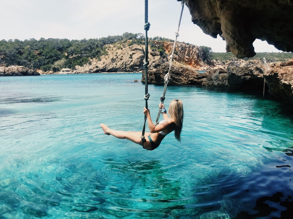A young woman swings on a rope swing above blue sea water