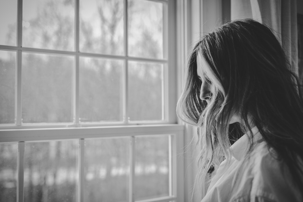 Black and white photo of a woman looking out of a window