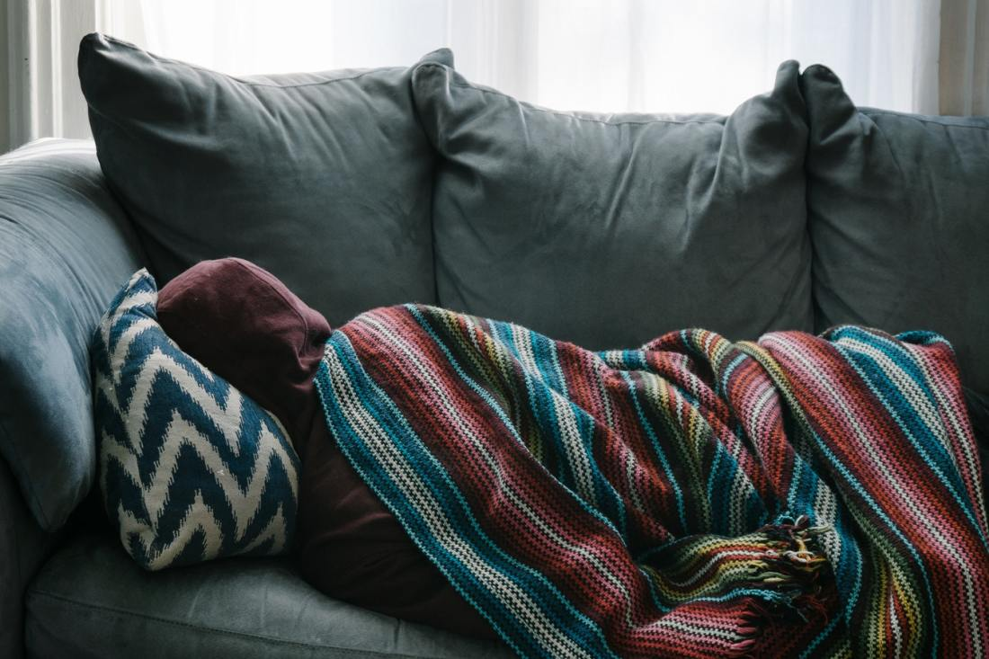 A person sleeps on a sofa underneath a blanket