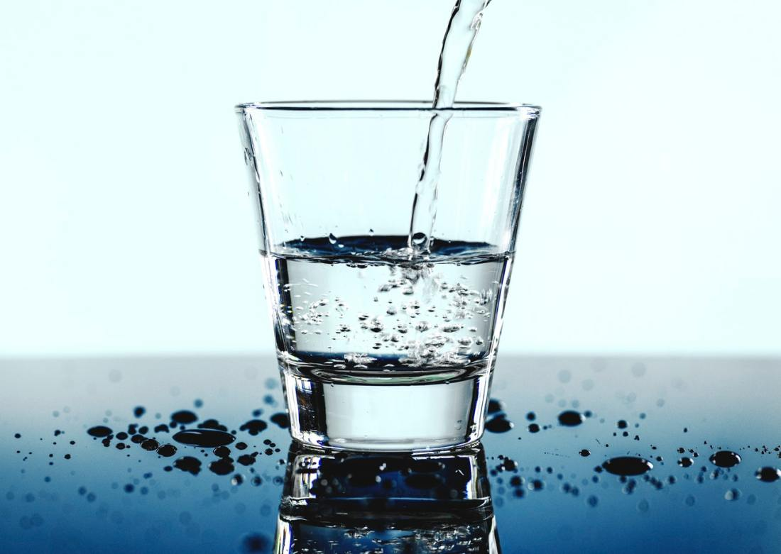 A glass of water against a blue background