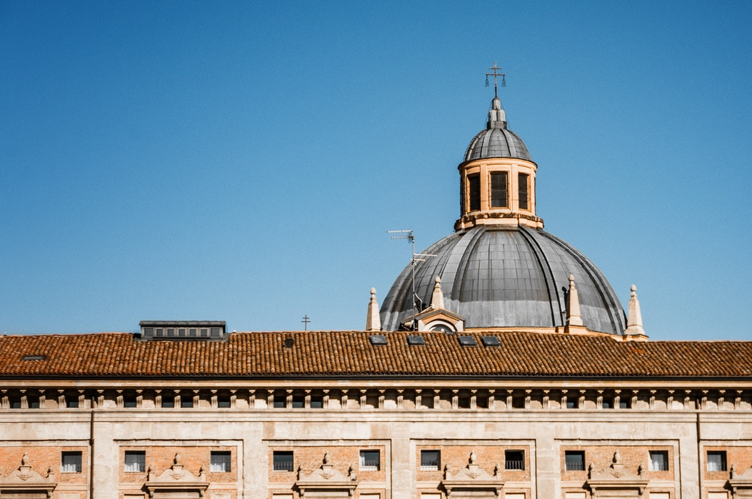 The dome of Bologna's cathedral visible above a building