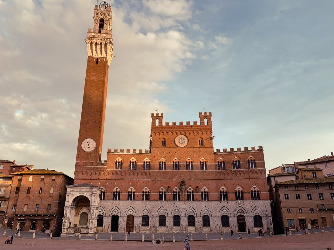 The central piazza in Siena, Italy, with a large building with a tall bell tower