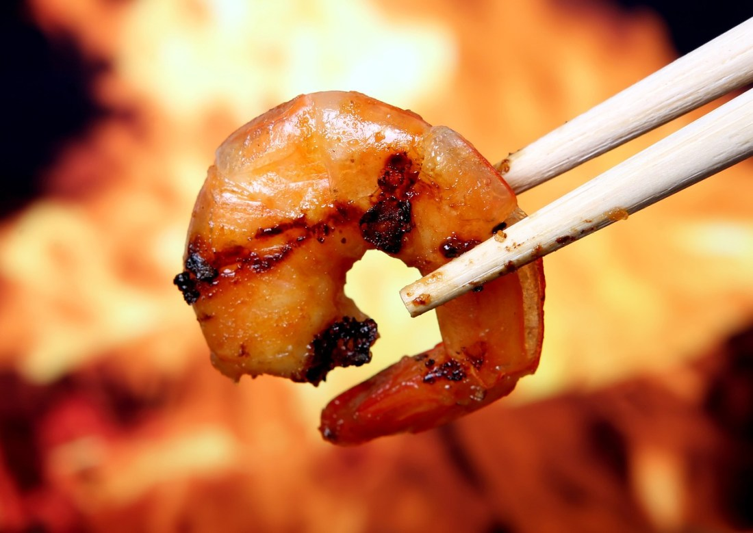 A barbecued prawn between chopsticks