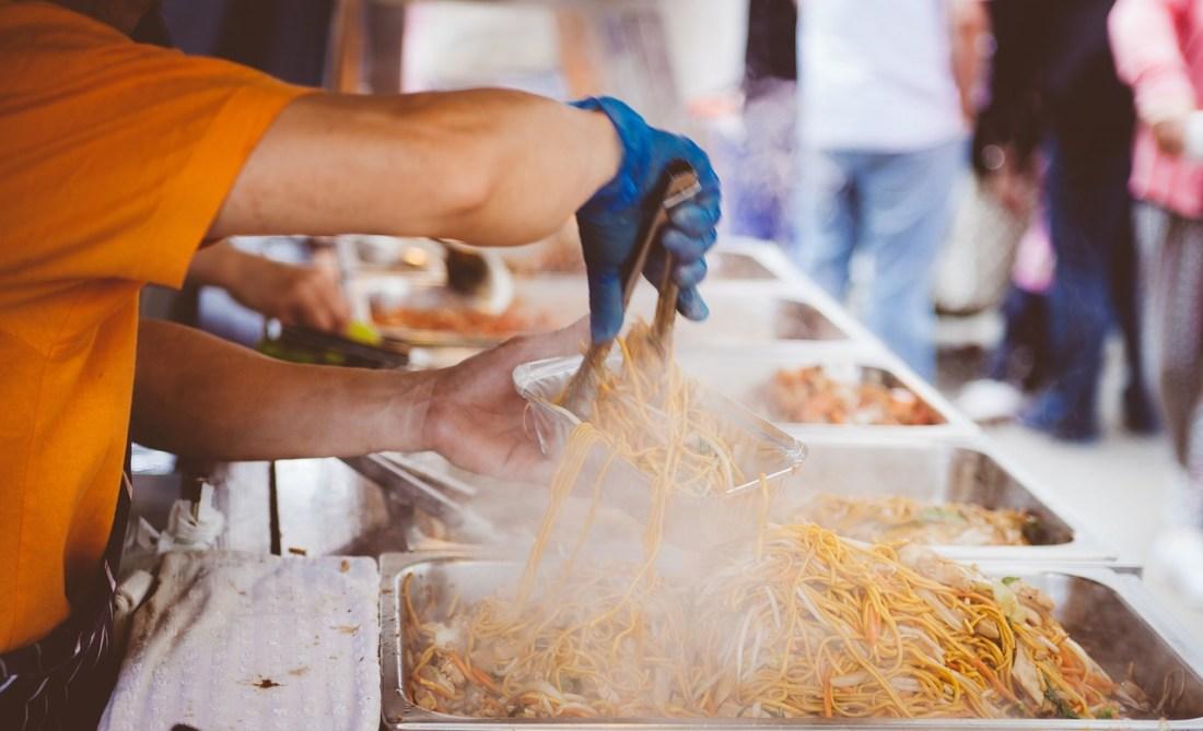 A street food vendor puts noodles in a bowl