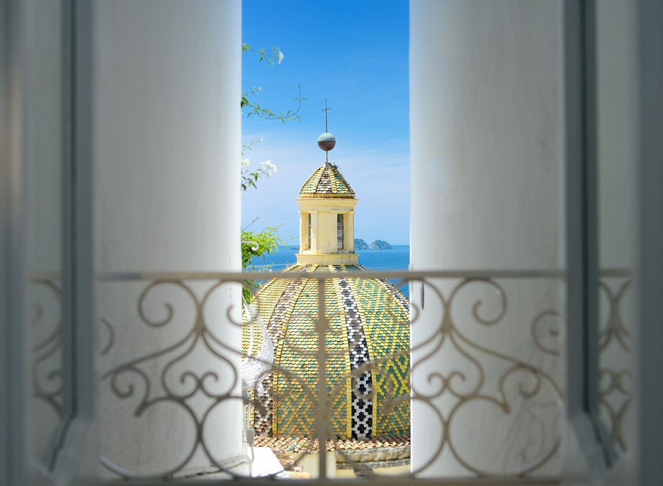 The dome of Positano's cathedral visible from a hotel window - The best hotels on the Amalfi Coast for all budgets