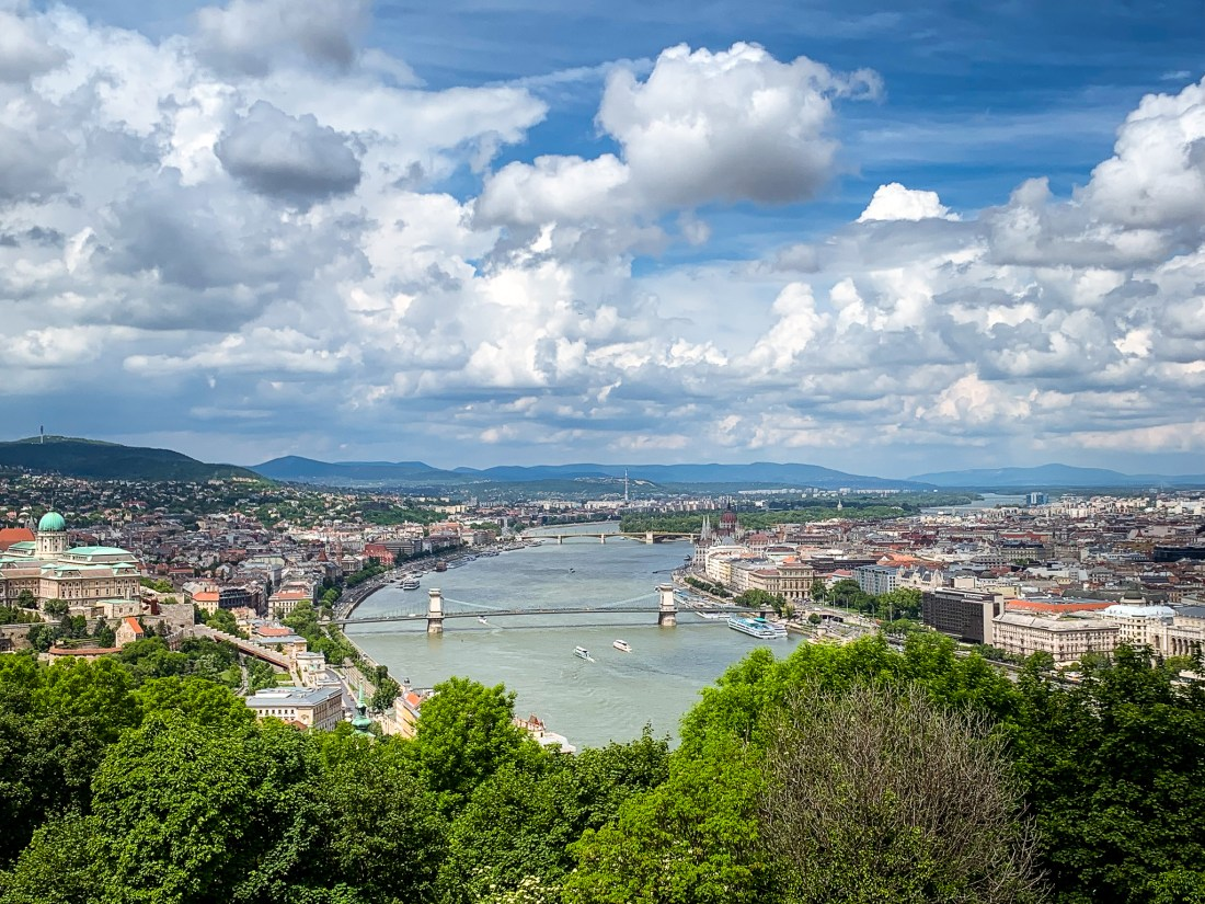A view of Budapest taken from Gellert Hill. The Danube river winds between the two cities of Buda and Pest, framed by greenery and distant hills.
