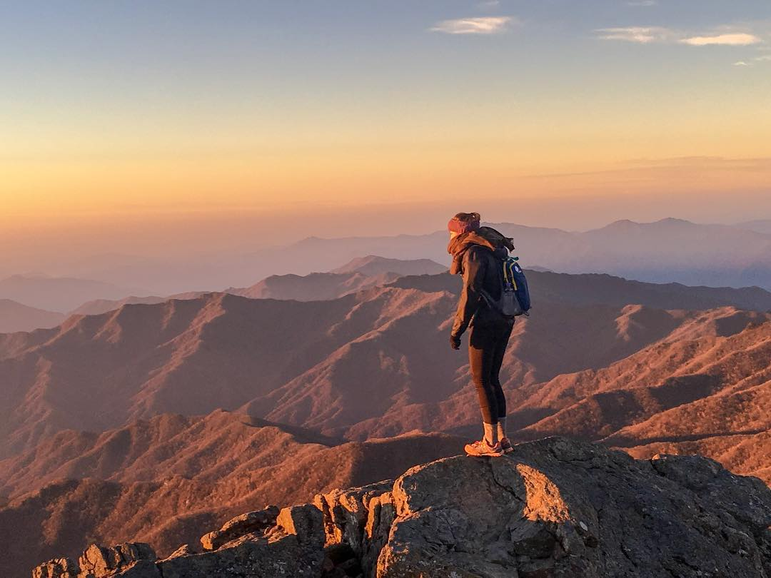 A woman stands at the peak of a mountain - How to Overcome Travel Anxiety - Travel Bloggers' Stories