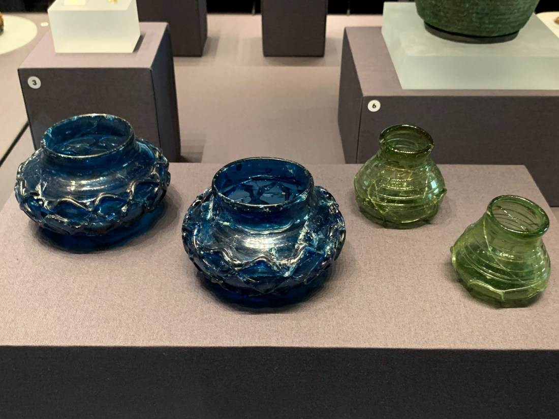 Blue and green glass beakers in a museum