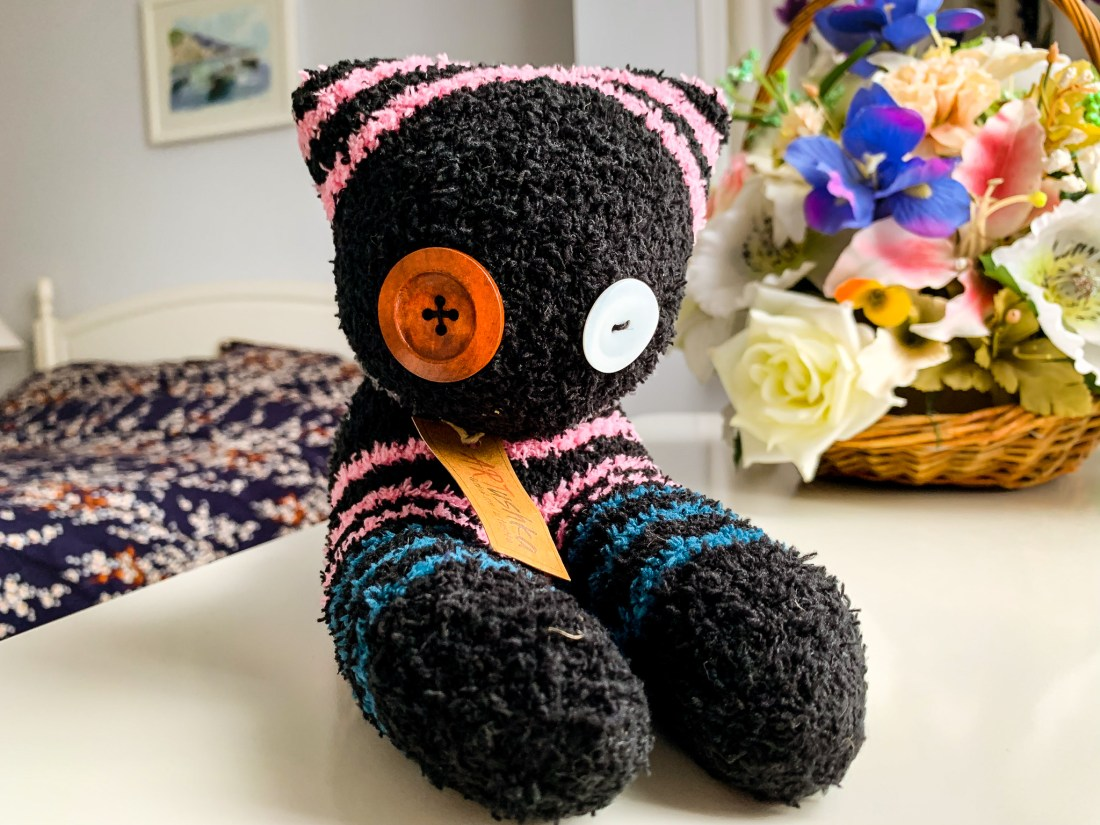 A toy cat made from socks, with button eyes